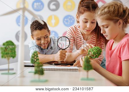 Studying Thoroughly. Upbeat Teenage Students Sitting At The Table And Examining A Little Tree Model