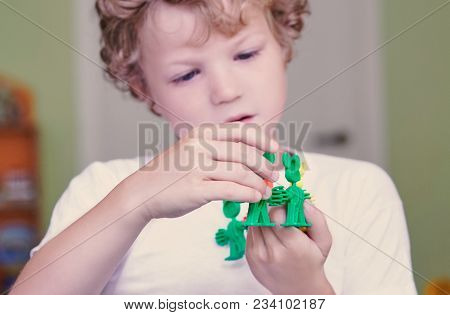 Cute Caucasian Boy In A White Shirt Playing With Colorful Constructor Details. Activities With Child