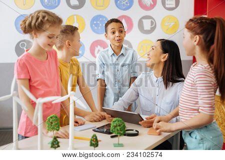 Friendly Ambience. Happy Schoolchildren Being Gathered Around Their Ecology Teacher Sitting At The T