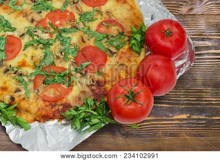 Fragment Of The Cooked Round Pizza With Tomatoes, Mushrooms, Arugula And Fresh Tomatoes Beside On An