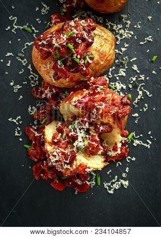 Baked Jacket Potatoes Topped With Red Kedney Beans In Tomato Sauce And Chives Served On Stone Board.