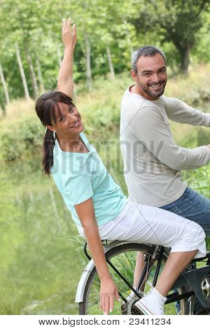 a couple doing bike in the country, the woman is doing airplane with her arms