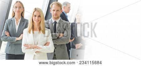 Successful business team with arms crossed at the office, white copy space