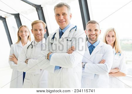 Successful team of medical doctors are looking at camera and smiling while standing in hospital with arms crossed