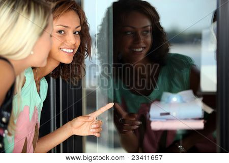 Two female friends window shopping
