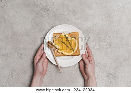 Partial Top View Of Person Holding Plate With Fresh Healthy Sandwich With Honey And Orange Slices On