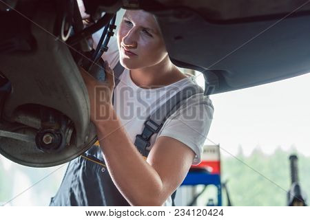 Low-angle view of a dedicated mechanic working hard at the modification of a car in a modern automobile repair shop with professional tuning services
