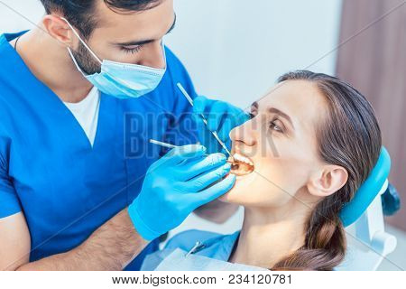 Young and beautiful woman looking with confidence at her reliable dentist during safe and painless dental treatment in a modern clinic