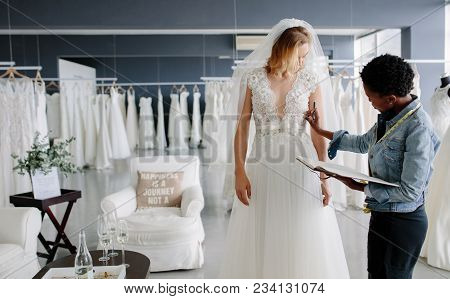 Dress Designer Fitting Bridal Gown To Woman In Boutique. Women Checking And Making Adjustment To Wed