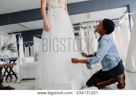 Woman Making Adjustment To Bridal Gown In Wedding Fashion Store. Bride In Her Wedding Dress With Fem
