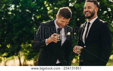 Groom And Best Man Drinking And Smiling During Wedding Party. Groom And Groomsmen Partying After Wed