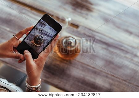Close Up Of A Woman Capturing Photos Of A Glass Teapot Using A Mobile Phone For Her Food Blog. Food