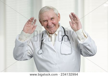 Senior Doctor Laughing Hard With Raised Hands Up. Doctor Is Kidding, Windows With Jalousies Backgrou