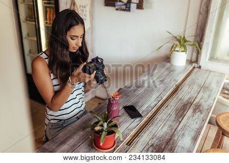 Woman Taking Photos Of A Smoothie Placed Beside A Flower Pot Using A Professional Camera For Her Foo