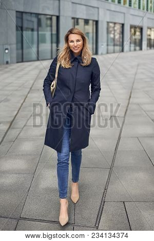 Attractive Stylish Slender Blond Woman In Jeans And An Overcoat Walking Along An Urban Street Lookin