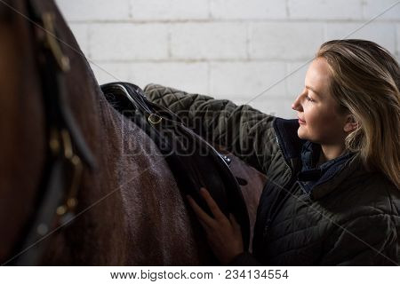 Female Owner Adjusting Saddle Straps In Stable With Horse