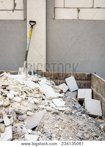 Trash Construction Building Demolition Waste Hard Work Concept. Spade In Pile Of Rubble. Manual Labo