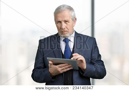 Portrait Of Smart Old Manager With Tablet. Company Header In Business Suit And Gadget, Bright Window