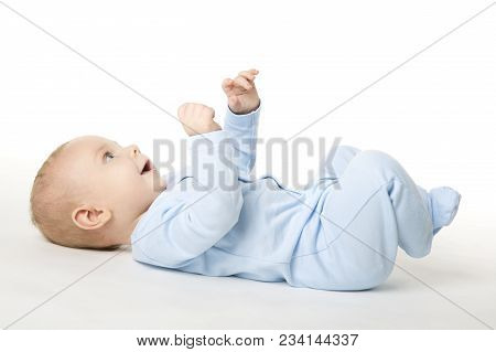 Baby Lying On Back, Happy Infant Kid Dressed In Blue Bodysuit, Beautiful Child Lie On White Backgrou