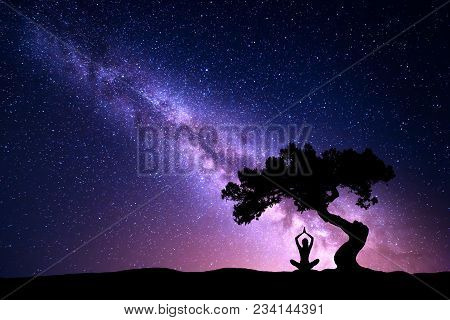 Milky Way With Tree And Silhouette Of A Sitting Woman Practicing Yoga. Beautiful Landscape With Medi