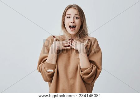 Excited Beautiful Blonde Young Female Gestures, Has Amazed And Happy Expression, Being Excited, Didn