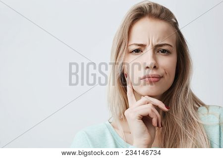 Horizontal Portrait Of Displeased Woman With Blonde Hair Has Indignant Expression Of Face, Frowns Ey