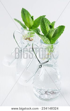 Green Young Mint Leaves In Bottle With Mineral Water On Soft White Wood Board. Summer Background, Ve