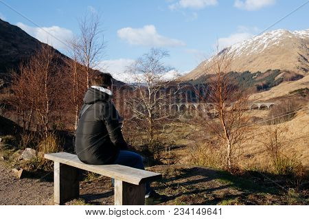 A Man Sits On A Wooden Bench, Looking At Glenfinnan Viaduct, Scotland, On A Sunny Spring Day.