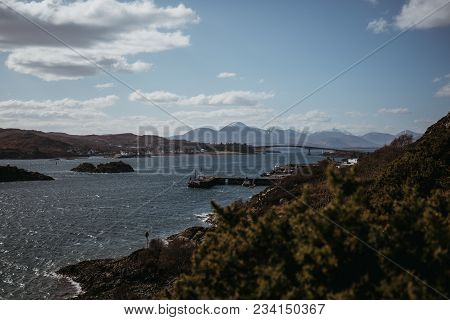 View Of Skye Bridge And A Small Coastal Village On Isle Of Skye, Scotland, On A Sunny Day. View From