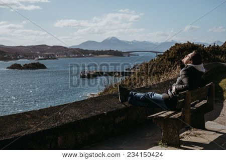 Man Sitting On A Bench, Relaxing In The Sun In Kyle Of Lochalsh, Scotland.  Skye Bridge And Isle Of