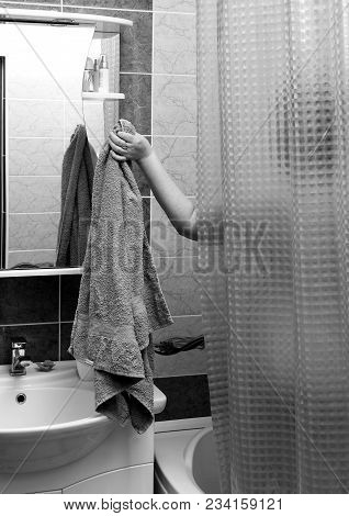 Black And White Photo. Girl Takes A Shower And Takes A Towel From Behind The Curtain.