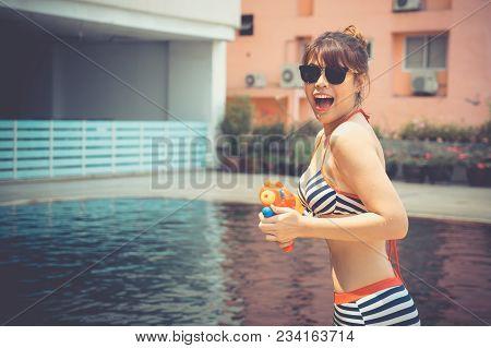 Pretty Lady Holding Plastic Water Guns At Pool Side Bikini Girl Friends Having Fun Together. Celebra