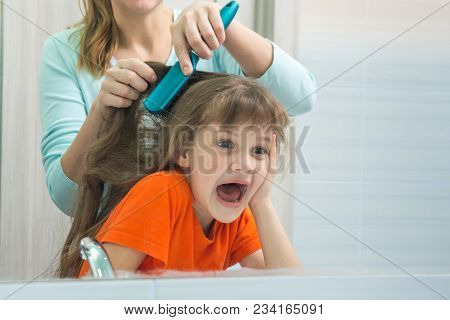 Mom And Daughter Are Having Fun While Mum Combing The Childs Hair