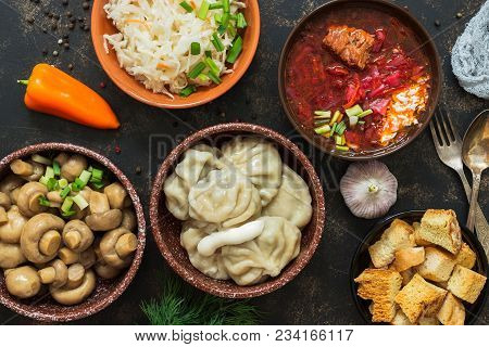 Russian Variety Of Dishes, Borsch, Dumplings, Pickled Mushrooms, Sauerkraut. Russian Food On A Rusti