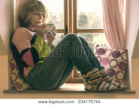 People, A Mature Woman Relaxing On A Window Seat With Pink Curtains And Cushions Drinking Tea