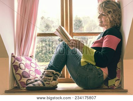People, A Mature Woman Relaxing On A Window Seat With Pink Curtains And Cushions Reading A Book