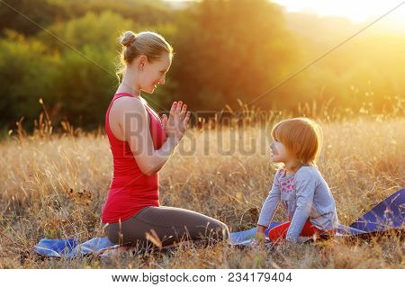 Mother Teaching Her Daughter To Practice Yoga Meditation