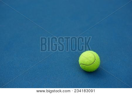 Yellow Bright Tennis Ball Is Lying On On Blue Carpet. Made For Playing Tennis. Contrast Image With S