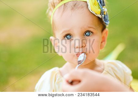 Little Girl Eats After Game Outside, The Hands Of The Mum With Spoon