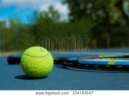 Close Up Of Tennis Ball On Professional Racket Background, Laying On Blue Tennis Court Carpet. Photo