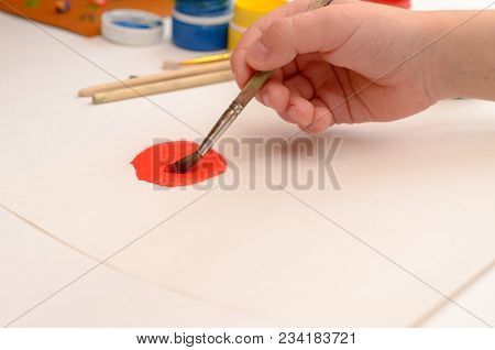 A Child's Hand Draws Gouache On White Paper With A Brush.