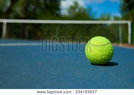 Yellow Bright Tennis Ball Is Lying On On Blue Carpet Of Opened Court During Sunny Day. Made For Play