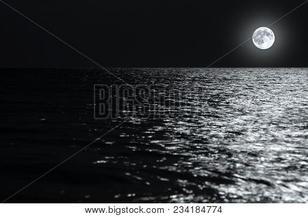 Moonlight On The Waves At Night In The Sea On Long Exposures. Black And White Photo.