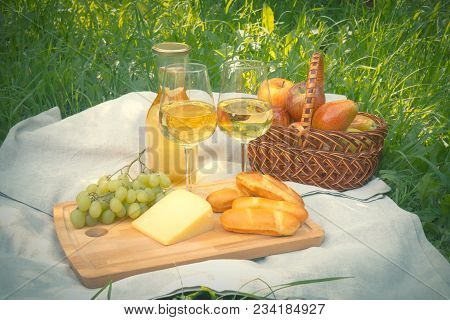 Picnic With Bottle And Glasses Of White Wine, Cheese, Bread  And Fruits