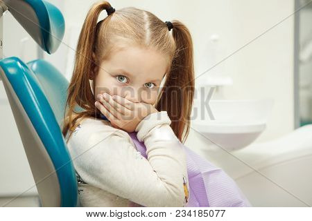 Little Child With Wide Open Green Eyes And Ginger Hair Sits At Dentist Office In Comfortable Leather