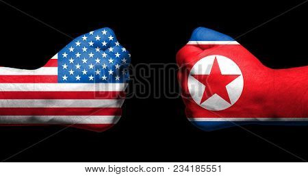 Flags Of Usa And North Korea  Painted On Two Clenched Fists Facing Each Other On Black Background/ T