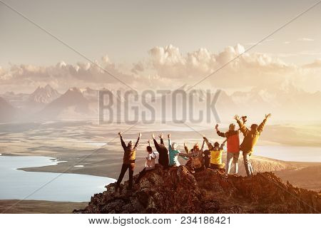 Big Group Of People Having Fun In Success Pose With Raised Arms On Mountain Top Against Sunset Lakes