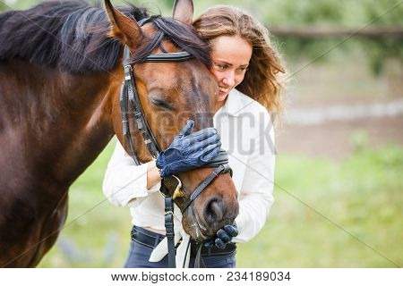 Young Happy Rider Woman With Her Bay Horse. Portrait Of Smiling Girl With Her Stallion In Paddock On