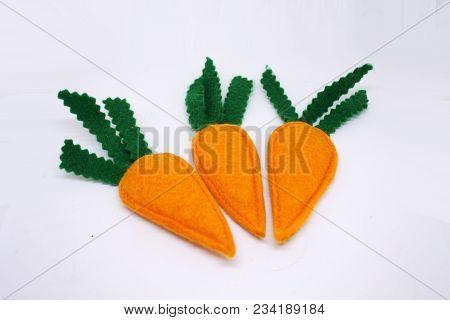Three Handmade Felt Carrots On White Background