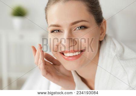 Young woman applying cream onto her skin, closeup
